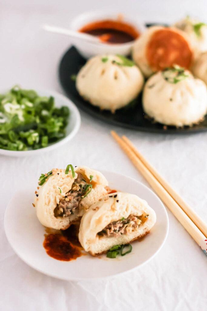 Cut Sheng Jian Bao on a white plate, with chopsticks.