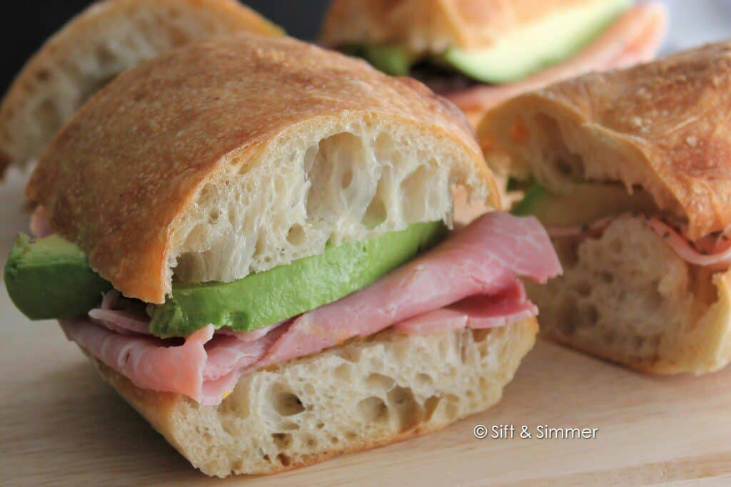 Cut baguette with ham and avocado in a sandwich.