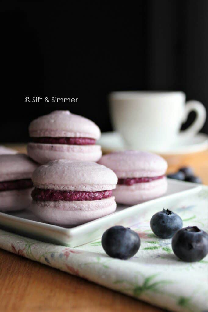 Vegan Blueberry Macarons on white square plate.