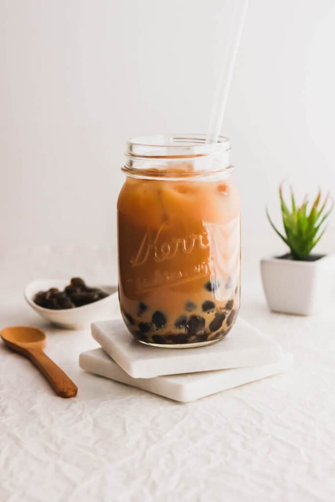 Glass of milk tea with boba on marble coasters.
