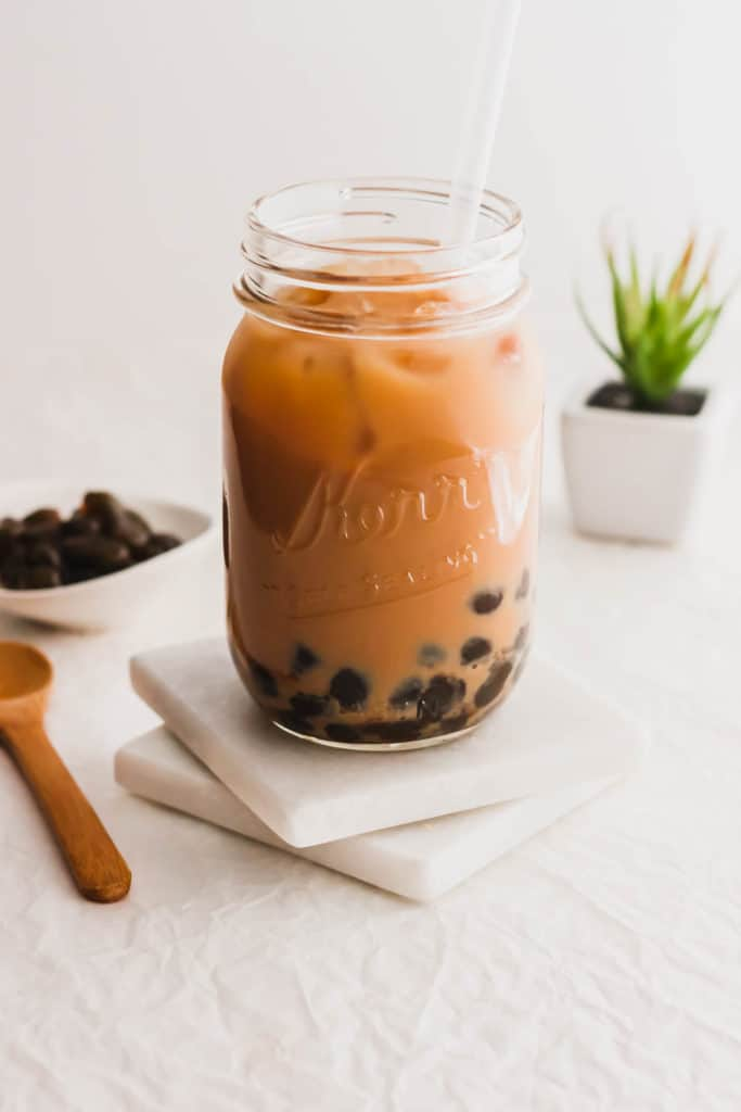 Milk tea with boba in glass jar with straw on marble coasters.
