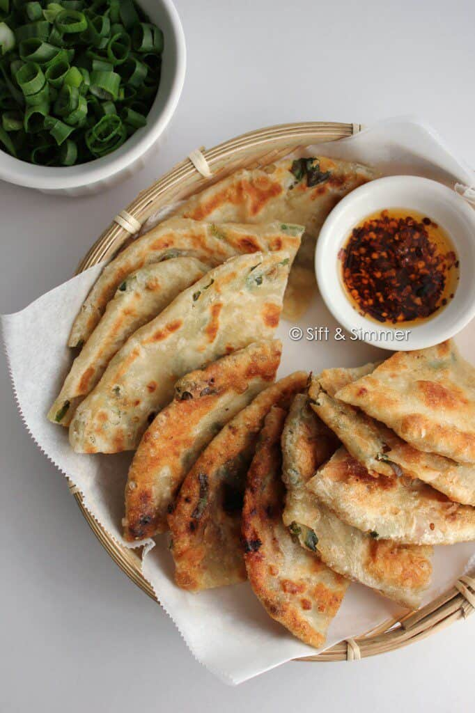green onion pancakes on bamboo tray with chili oil.