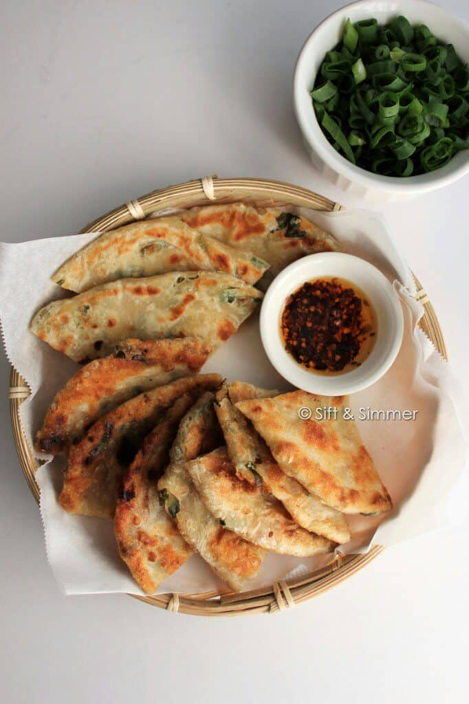 Cut up green onion pancakes on bamboo tray with dish of chili oil.