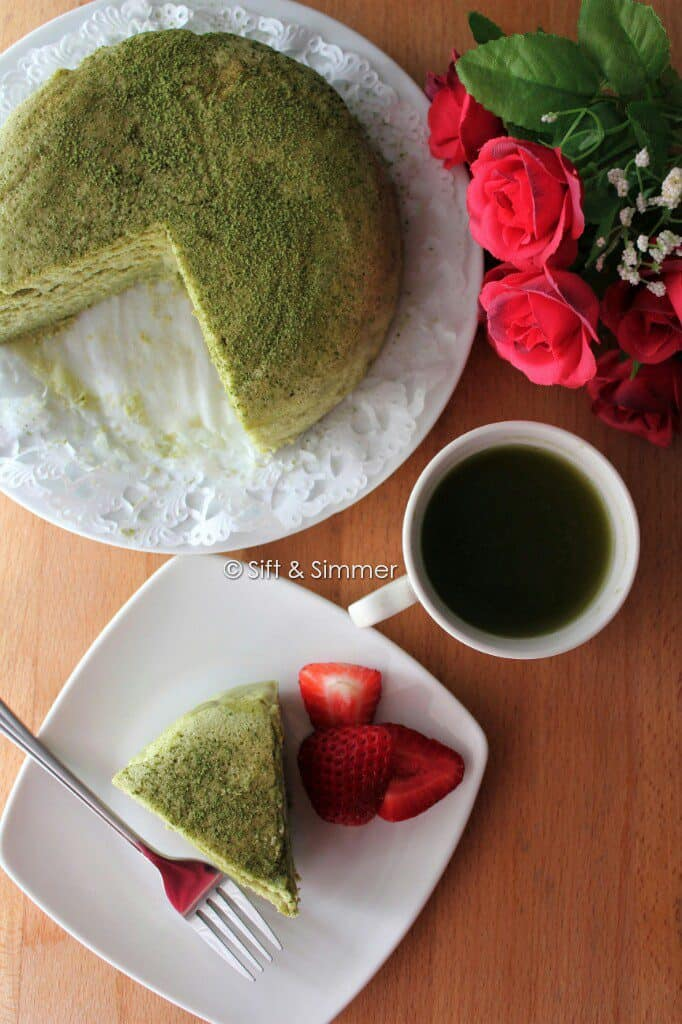 Matcha Cotton Cheesecake on plate with fork, tea cup.