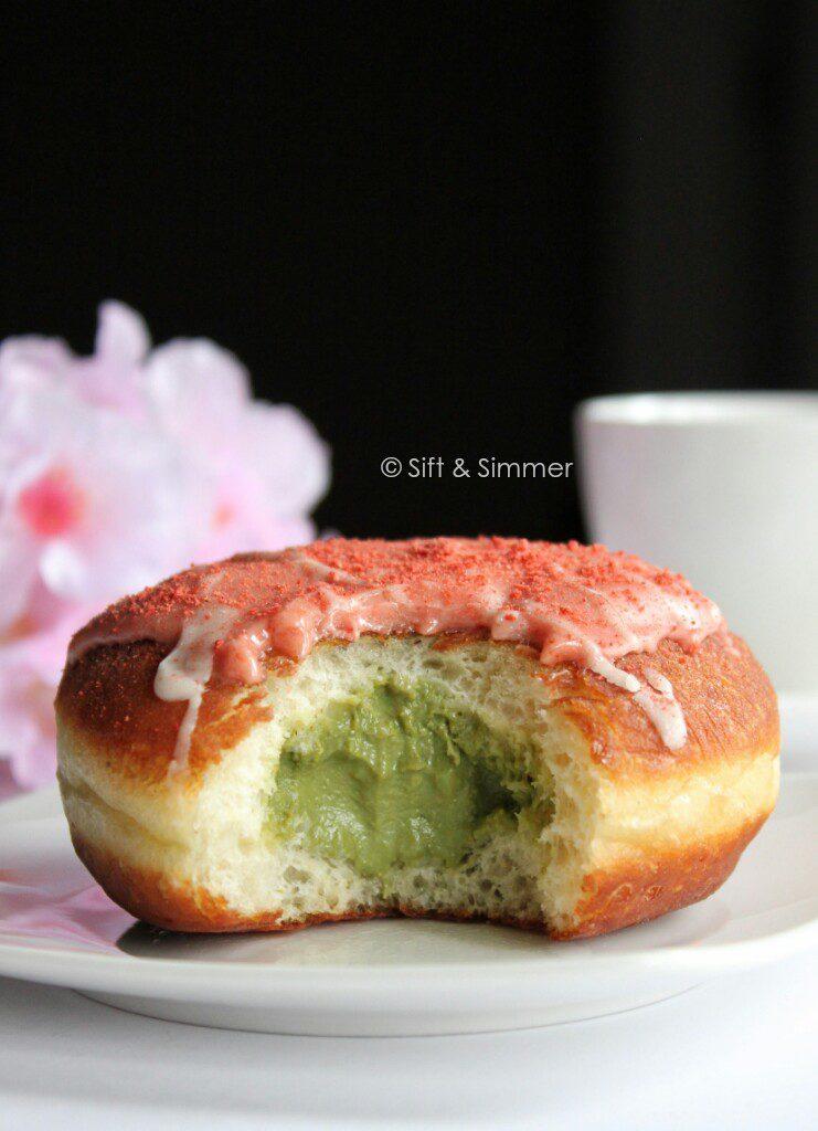 Bitten Strawberry Doughnut revealing matcha filling on white plate.