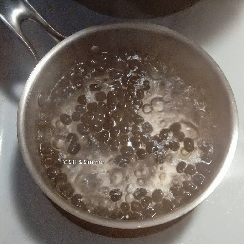 Black tapioca pearls boiling in water.