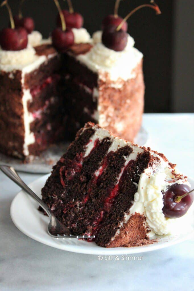 Slice of Black Forest Cake on white round plate.