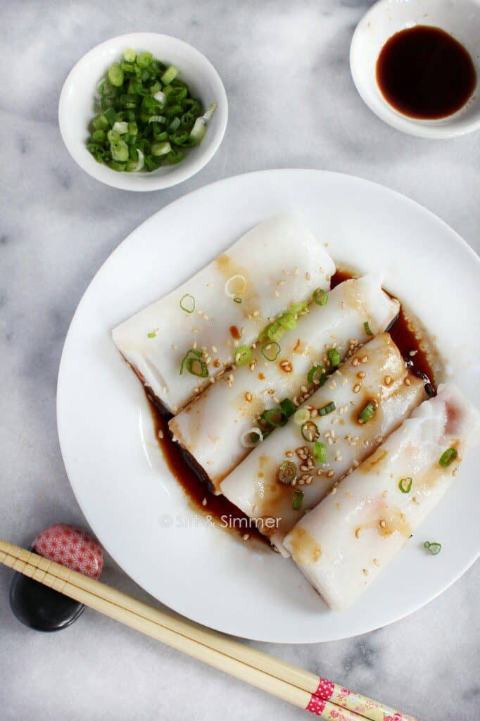 Rice Noodle Rolls on white plate, with chopsticks on side.