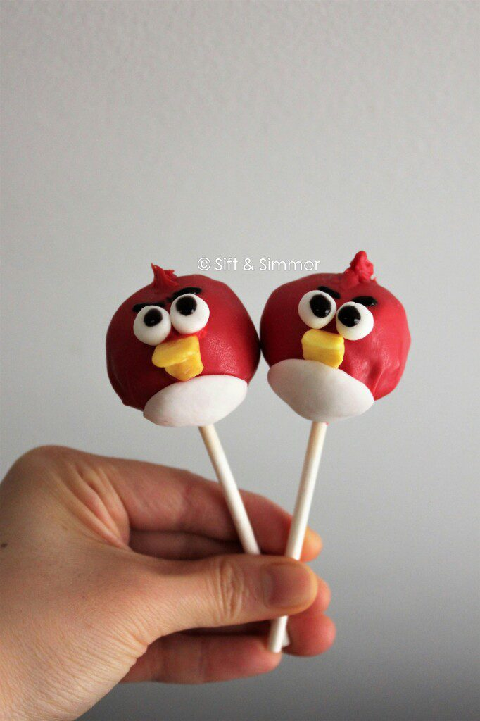 2 Angry Bird Cake Pops in hand.