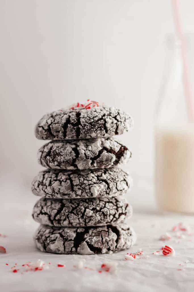 Stack of Chocolate Peppermint Crinkle Cookies with milk in background.
