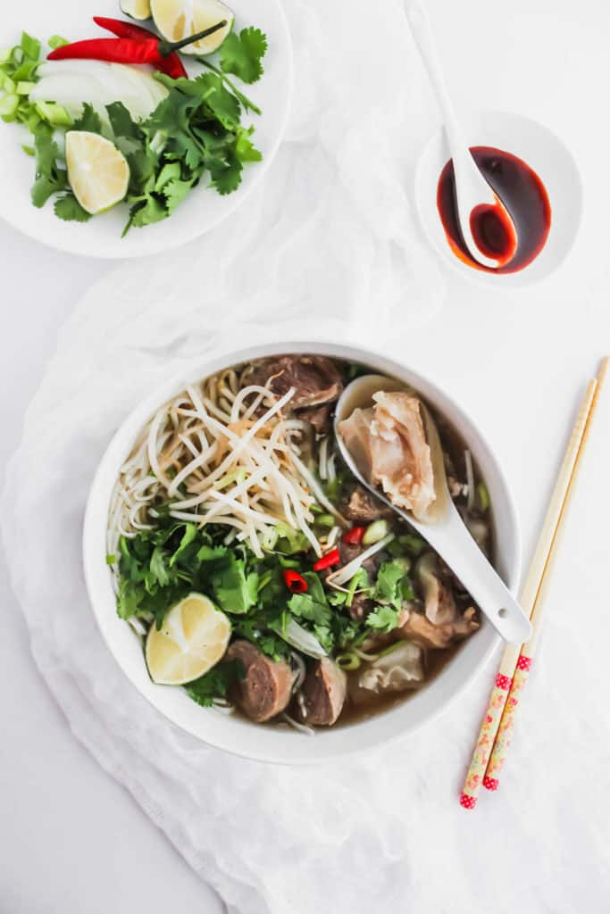 Instant Pot Beef Pho in a bowl with spoon, chopsticks, condiments.