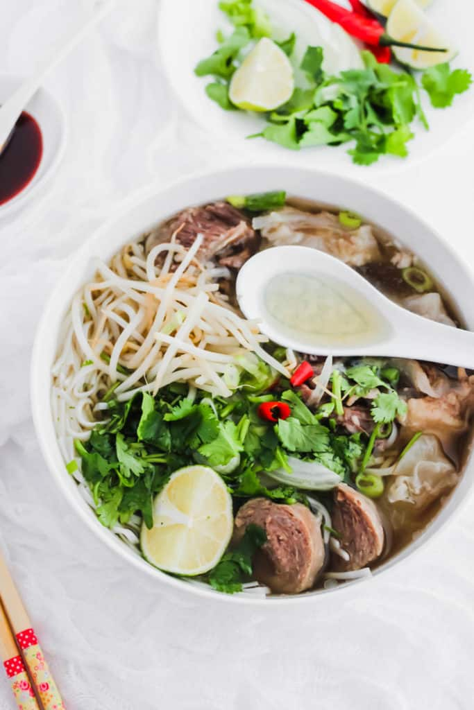 Close up of Beef Pho in a bowl with spoon.