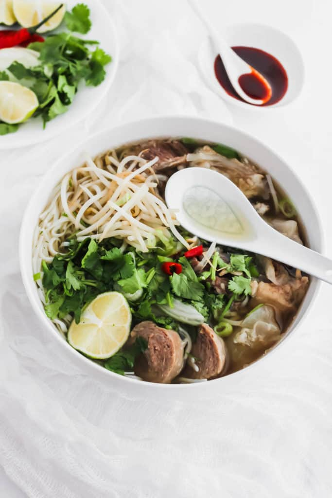 Instant Pot Beef Pho in a bowl with spoon.