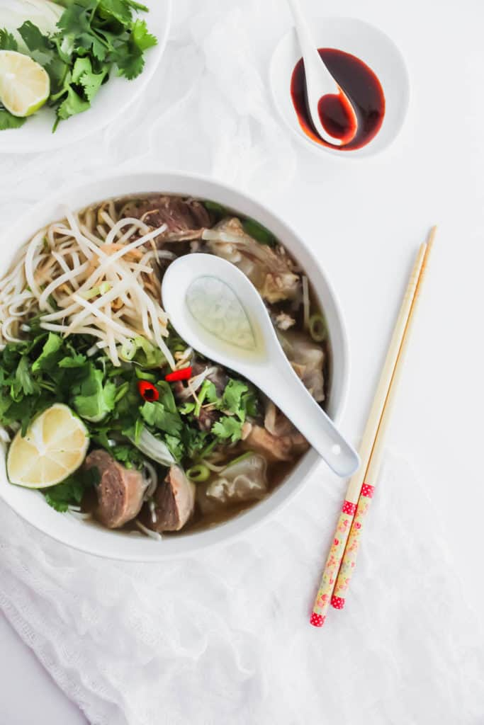 Instant Pot Beef Pho in a bowl with spoon and chopsticks.
