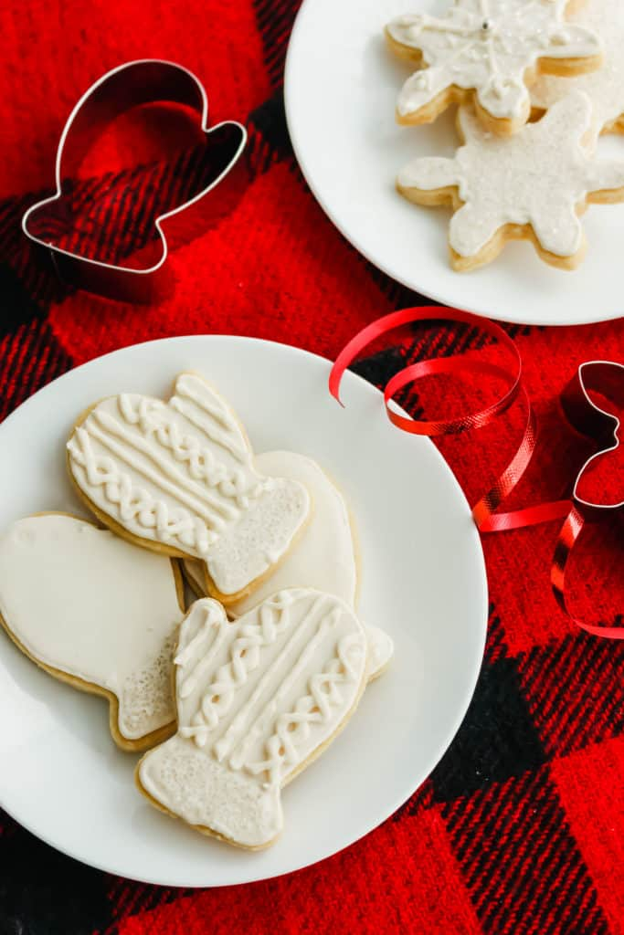 Sugar Cookies on a white round plate, on red plaid background.