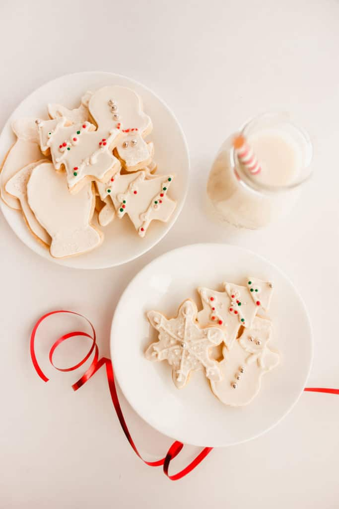 Sugar Cookies on a white round plates with red ribbon, glass of milk.