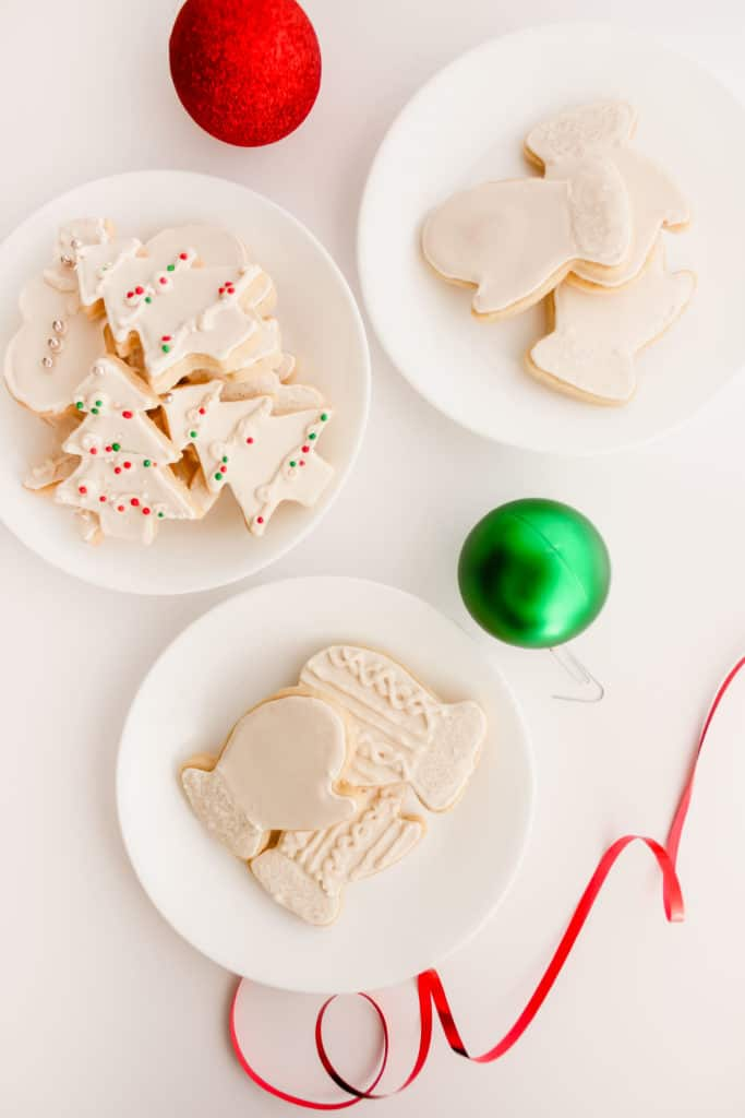 Sugar Cookies on white round plates, with festive ornaments.