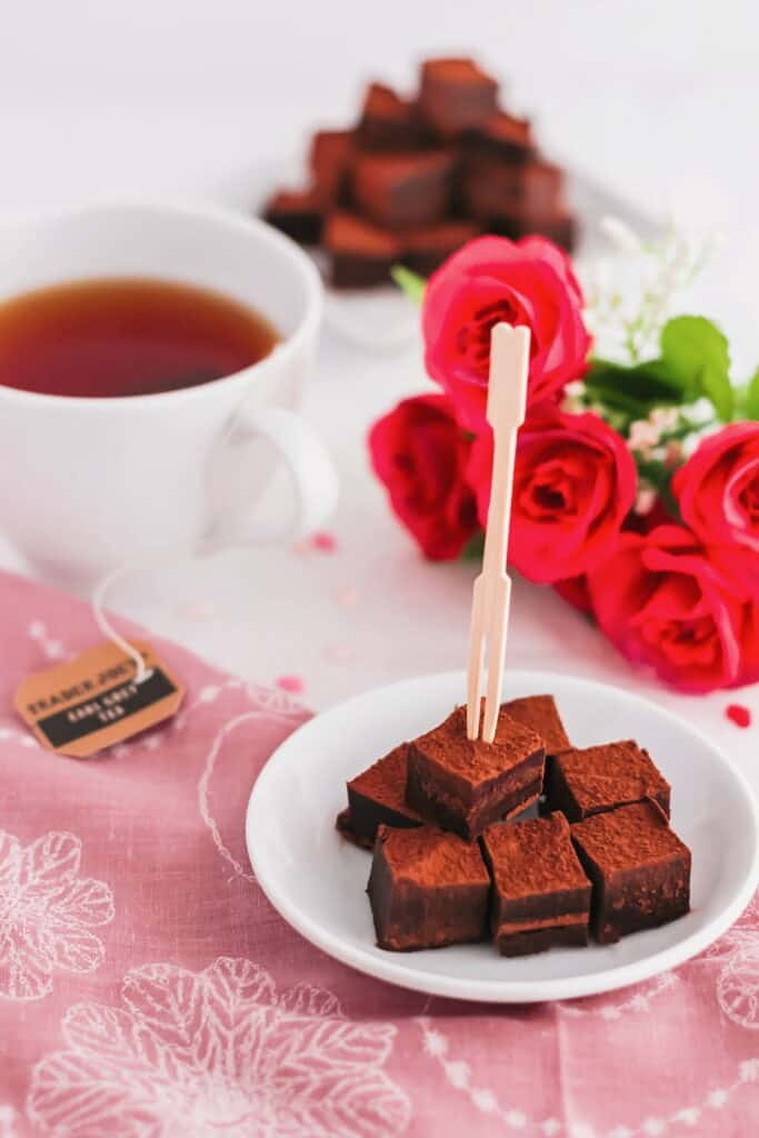 Cut Earl Grey Nama Chocolates with toothpick on small white dish.