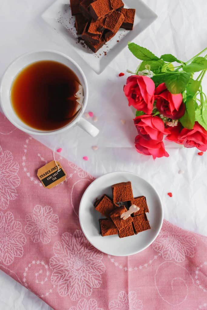Earl Grey Nama Chocolates with toothpick on small white dish, tea cup and flowers on side.