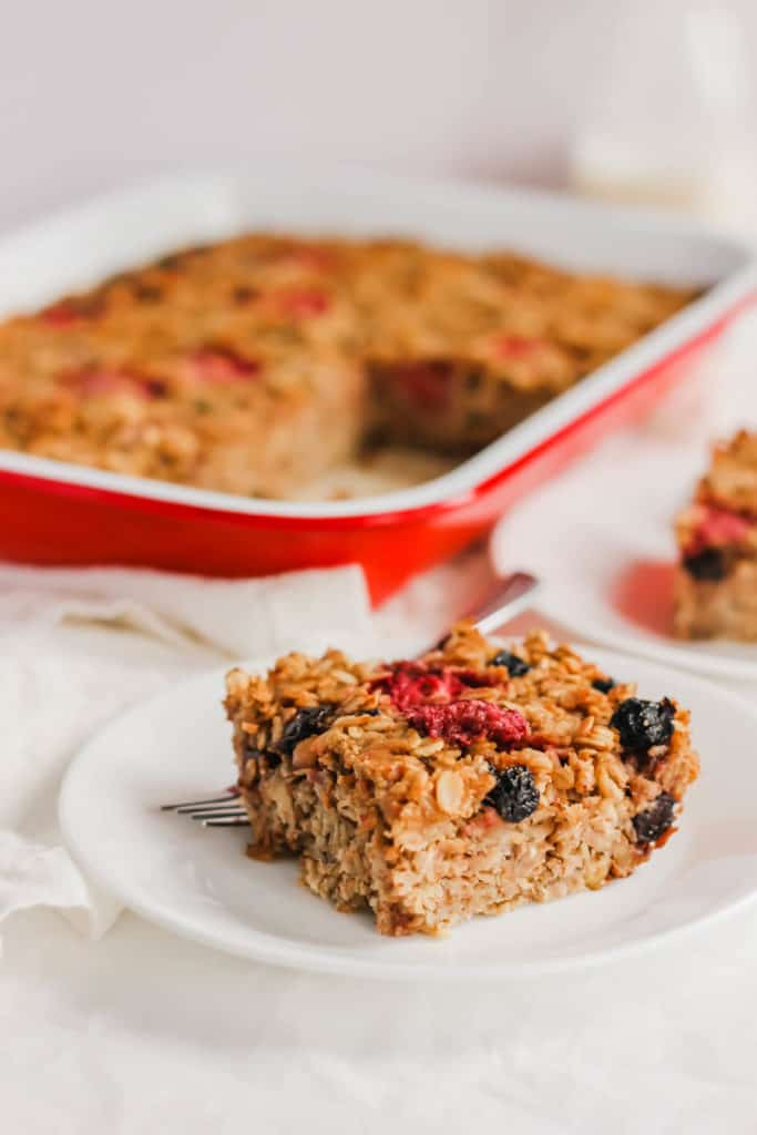 Slice of Baked Strawberry Oatmeal on white plate with fork.