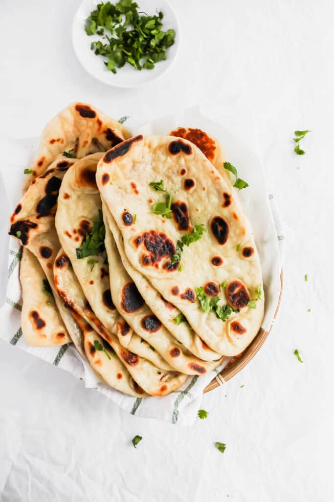 Soft & Fluffy Naan on a kitchen towel with cilantro sprinkled around.