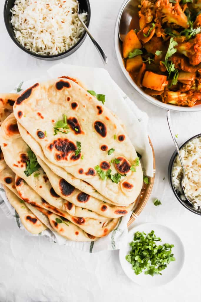 Soft & Fluffy Naan on a kitchen towel with aloo gobi, rice on side.