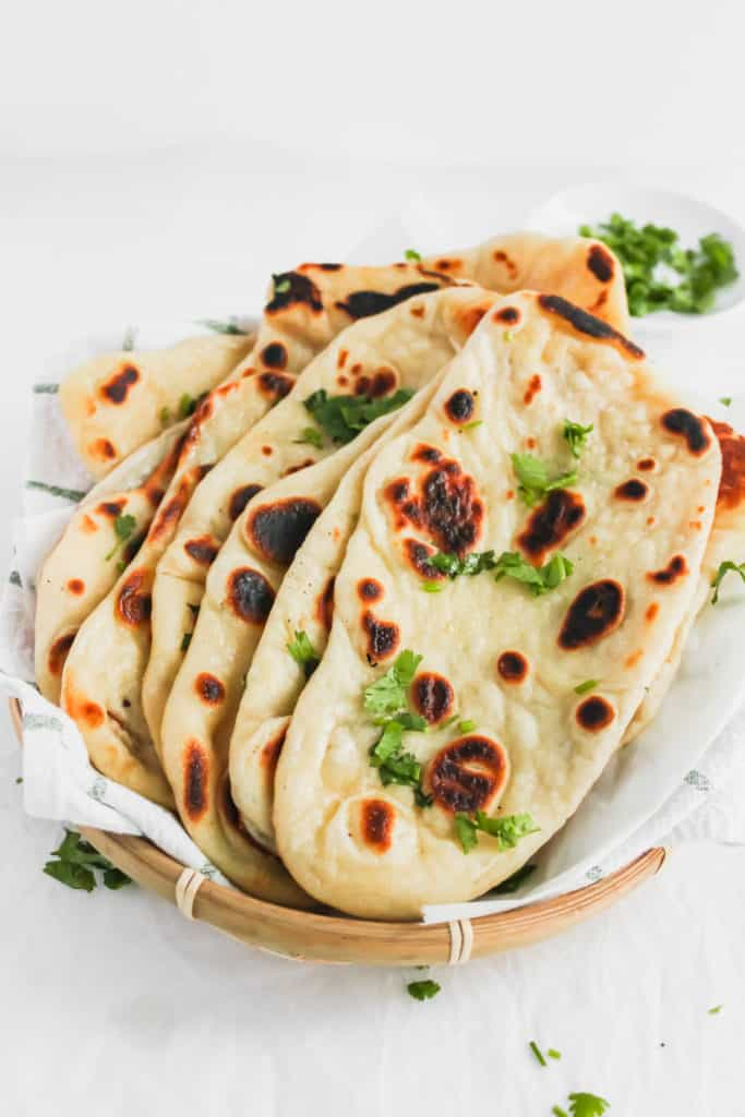Close up of Soft & Fluffy Naan on a kitchen towel with cilantro sprinkled around.