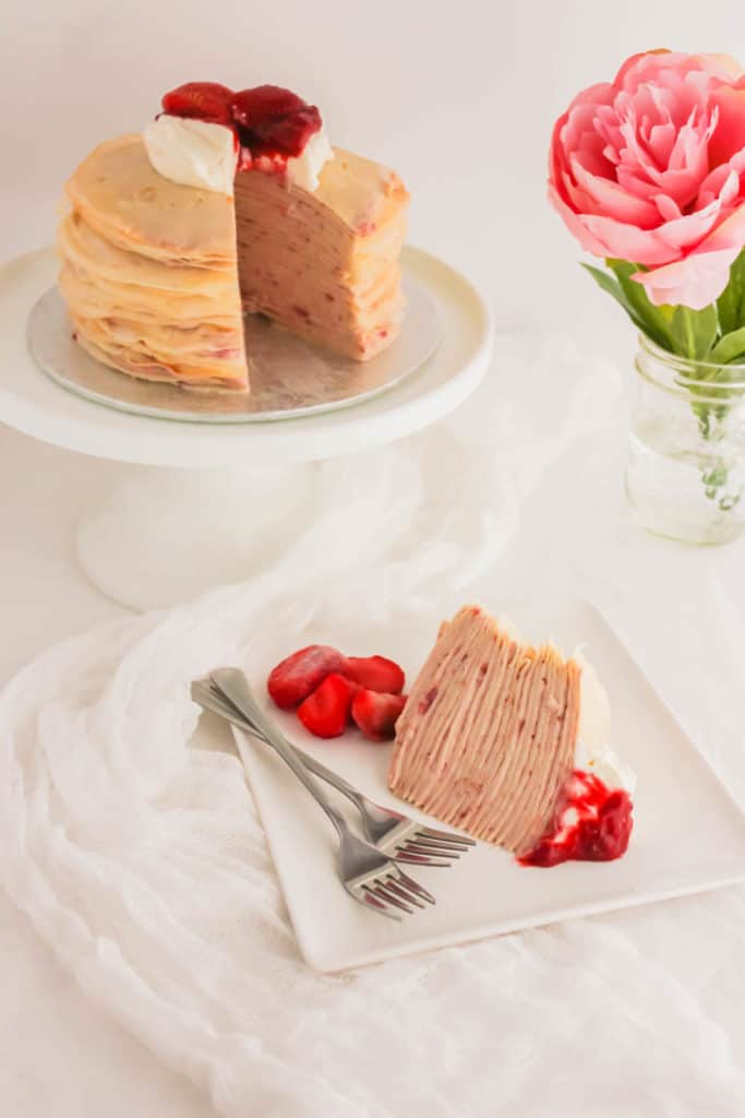Slice of Rose Strawberry Hibiscus Mille Crepe Cake on white square plate with forks.