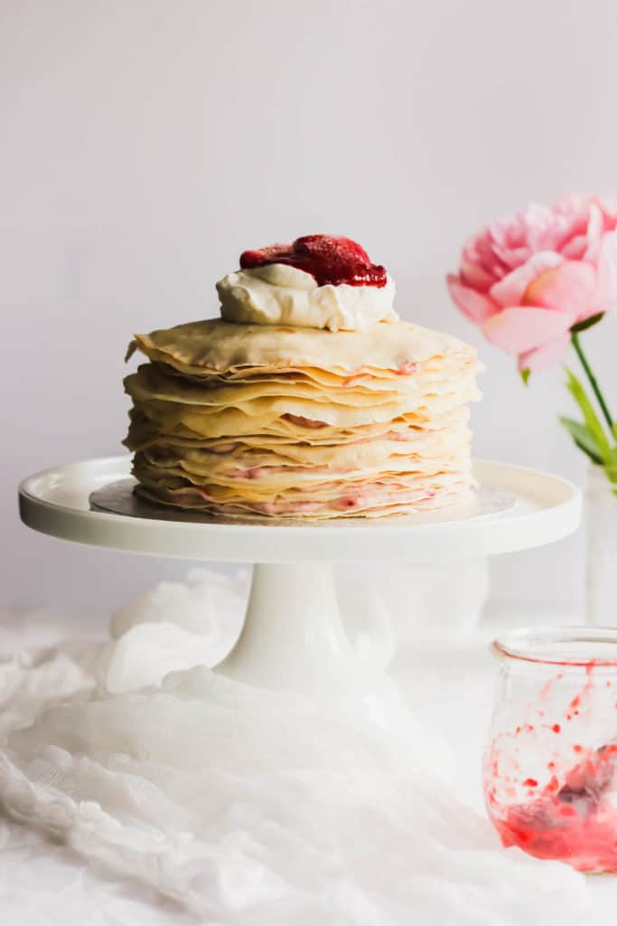 Rose Strawberry Hibiscus Mille Crepe Cake on white cake stand.
