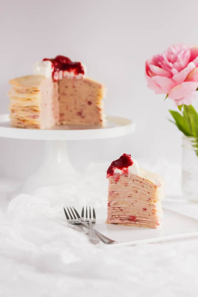 Slice of Rose Strawberry Hibiscus Mille Crepe Cake on square plate with forks.
