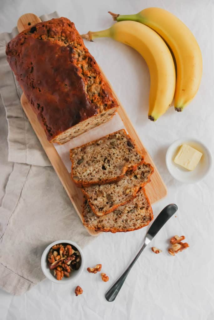 Sliced Banana Bread on wooden board with knife, butter, bananas.