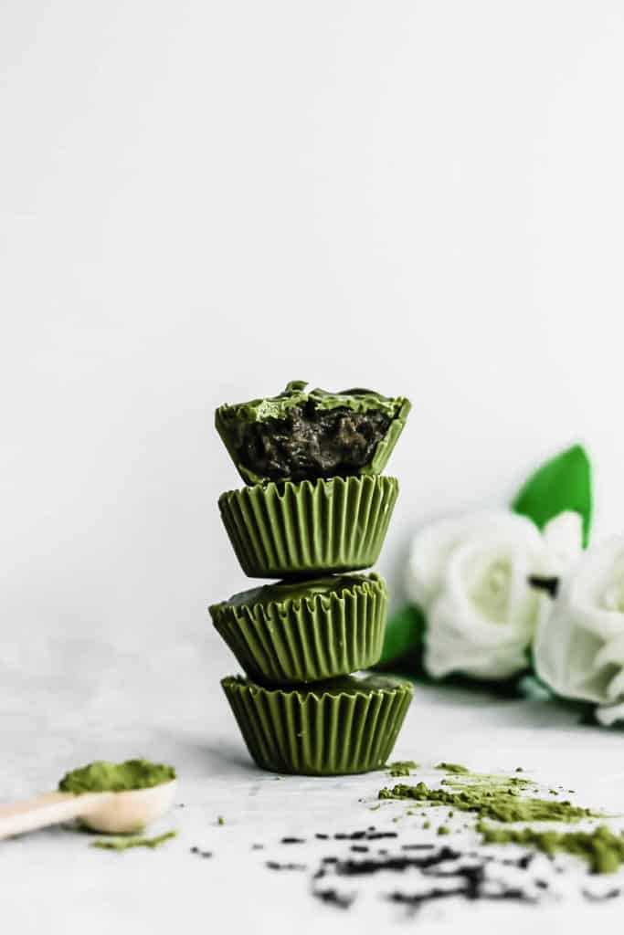Stack of Matcha Black Sesame Cups, with the top one bitten to reveal interior.
