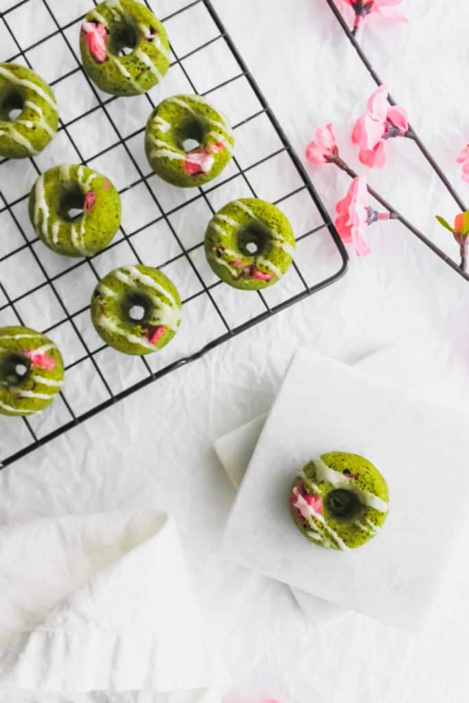 Sakura Cherry Blossom Matcha Doughnuts on marble coasters and cooling rack.