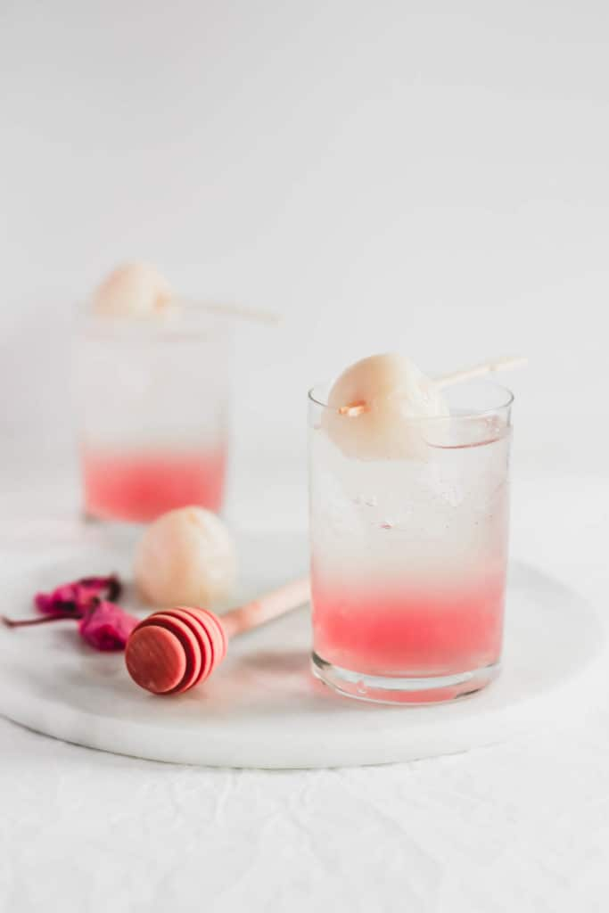 Glass of Sakura Lychee Fizz with lychee on a stick, on marble trivet.