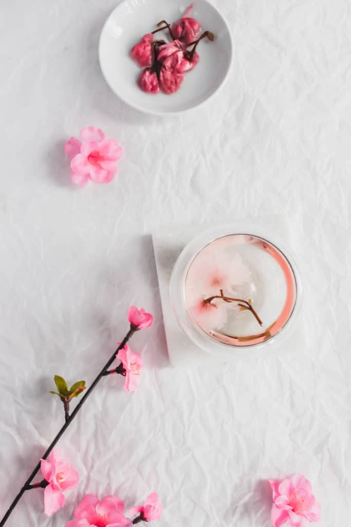 Sakura Cherry Blossom in tea cup, with cherry blossoms in dish.
