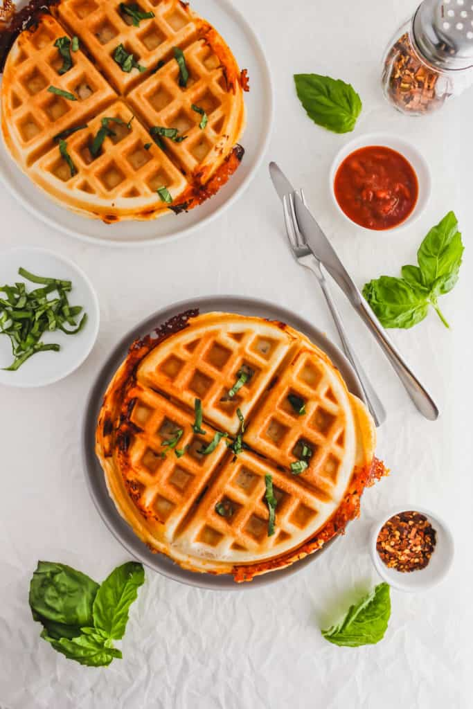 Pizza Waffles on grey plate with fork and knife.