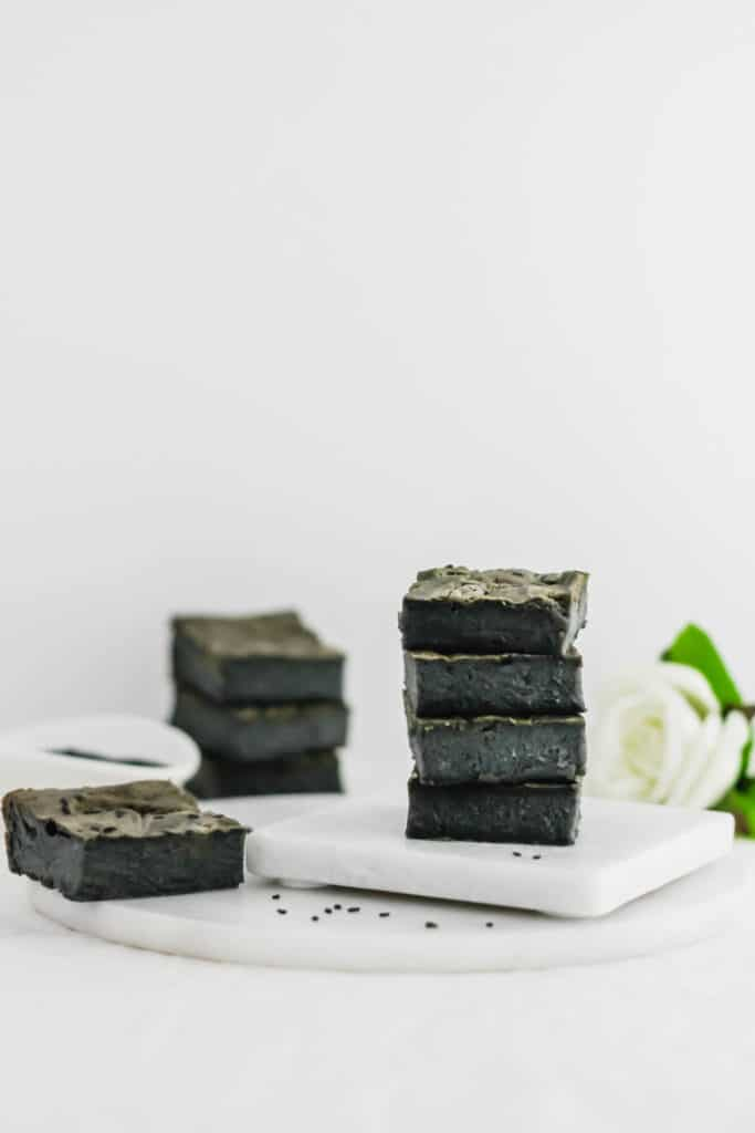 Stack of Black Sesame Charcoal Mochi on coaster on marble trivet, with black sesame seeds in small dish.