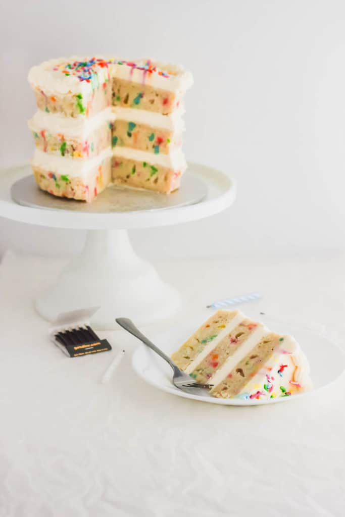 Slice of funfetti cake on white plate with fork, cake on white cake stand in background.