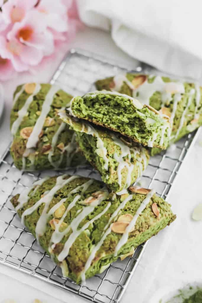 Close up of torn open Matcha Almond Scones on cooling rack.