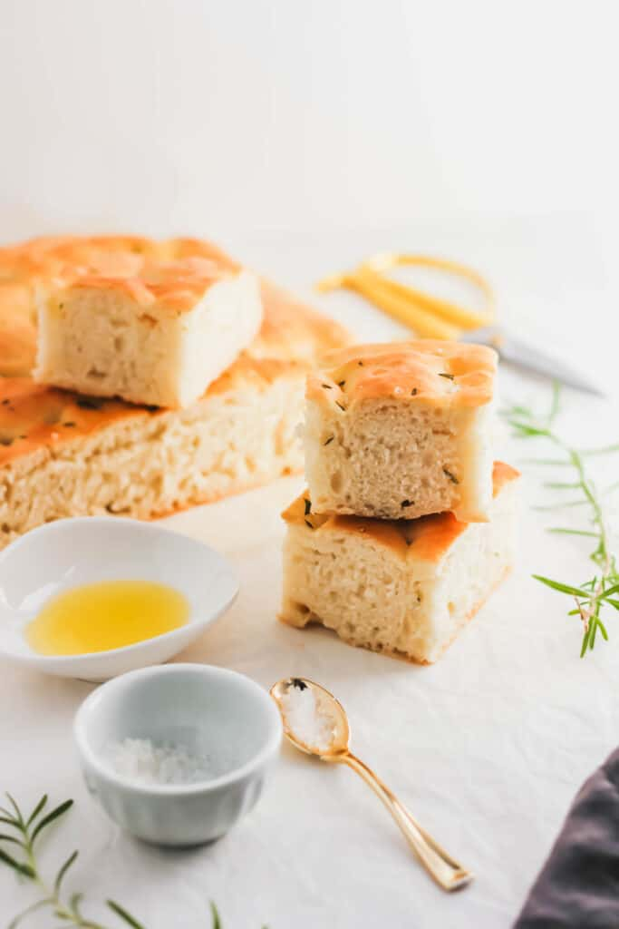 Stack of focaccia bread with olive oil in small dish, salt in small bowl.