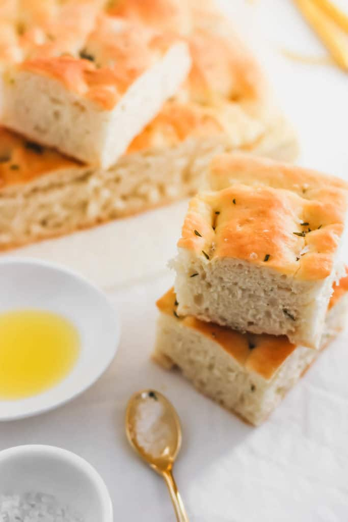 Close up of stack of focaccia bread with olive oil in small dish, salt in spoon.