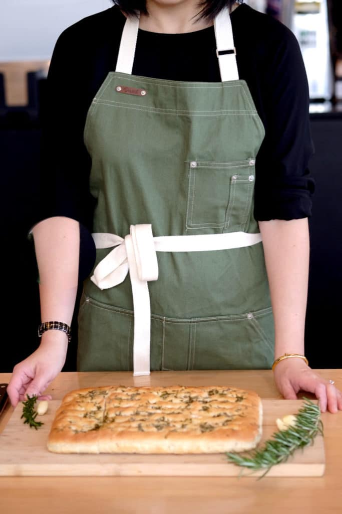Wearing green apron from Chef & Co with foccaccia on wooden board.