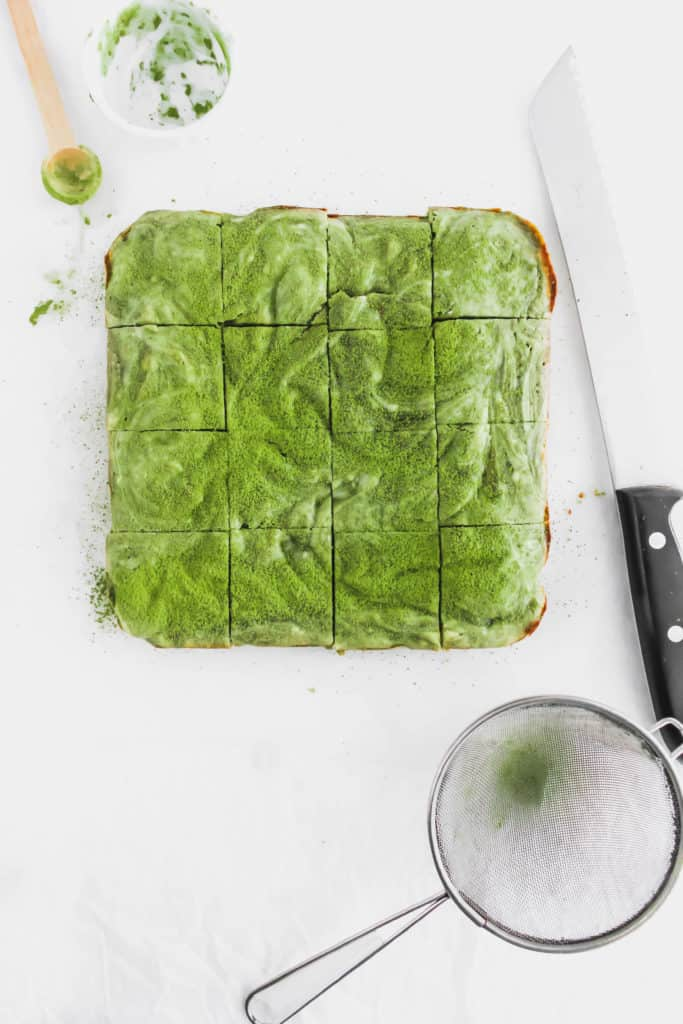 Matcha Cheesecake Brownies with knife.