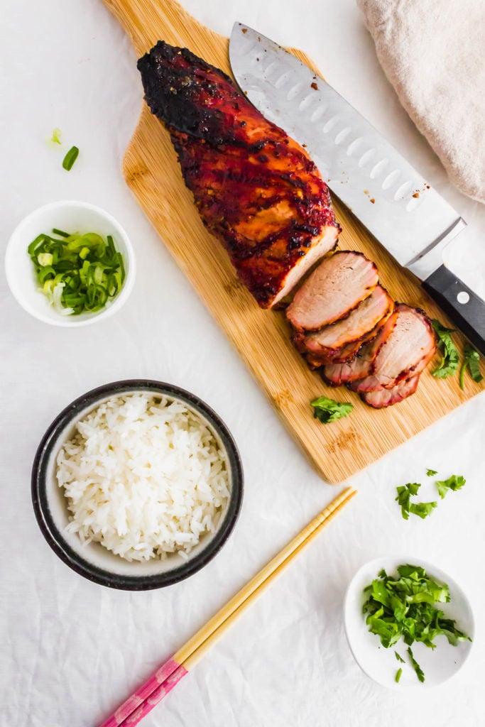 Roasted char siu bbq pork on wooden board, bowl of white rice, chopsticks, green onions..