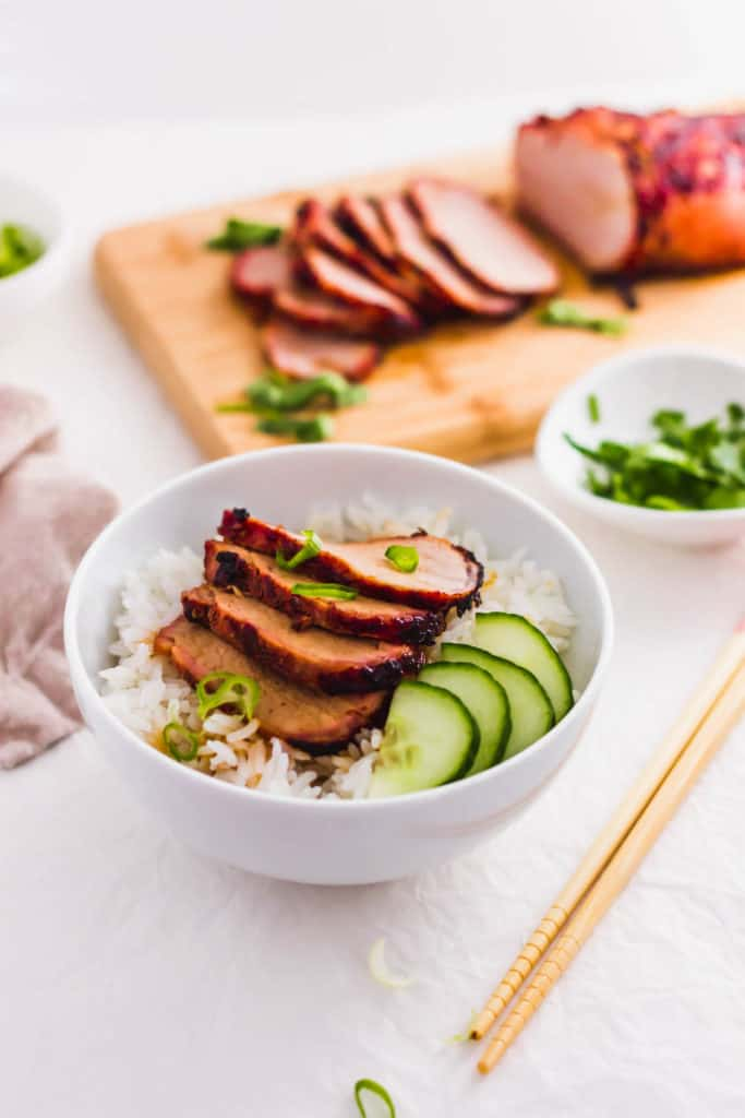 Roasted char siu bbq pork on top of rice in white bowl.