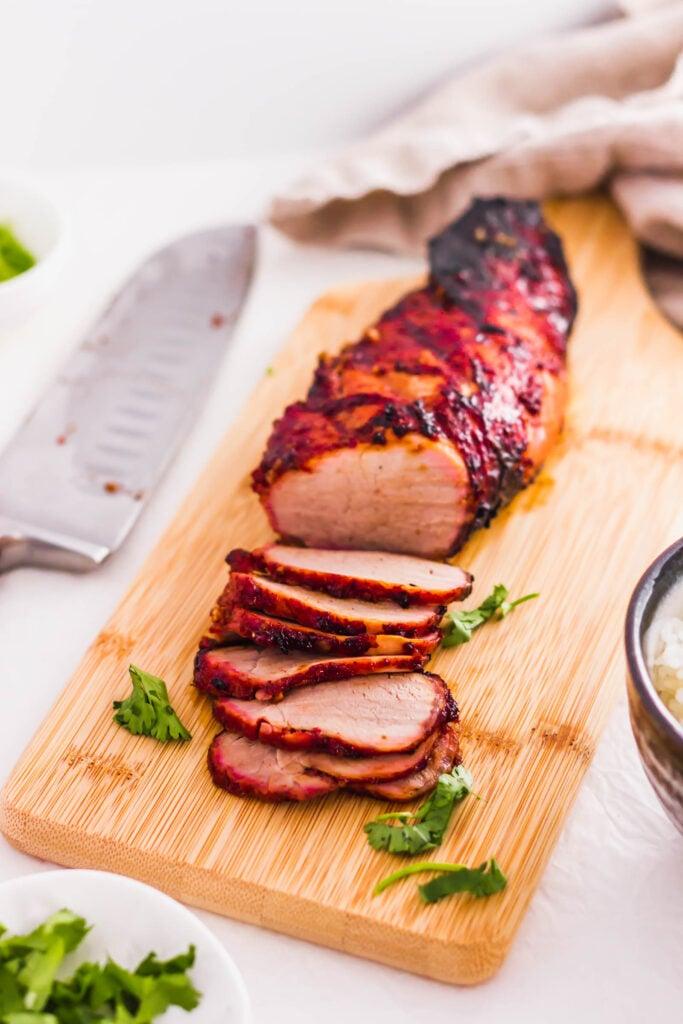 Roasted char siu bbq pork on wooden board.