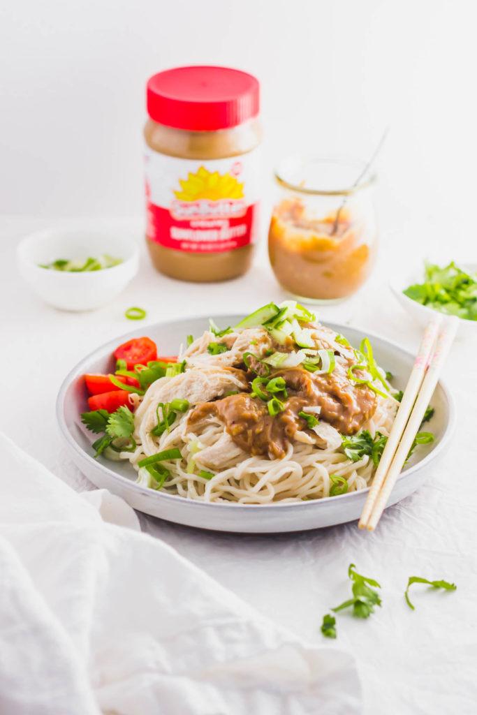 Sunbutter Chicken Noodles with Cucumber on round plate with chopsticks, SunButter jar in background.