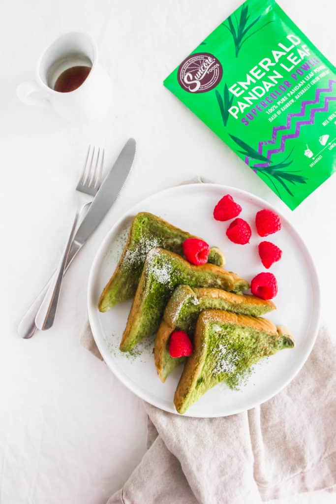Close up of Pandan French Toast on round white plate with raspberries and fork, packaging on side.