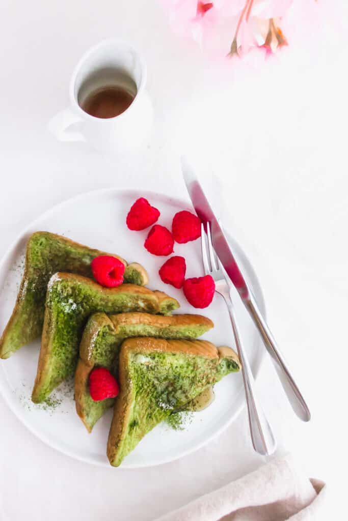 Close up of Pandan French Toast on round white plate with raspberries and fork.