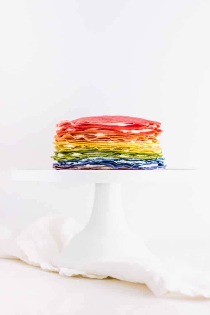 Rainbow mille crepe cake on white cake stand.